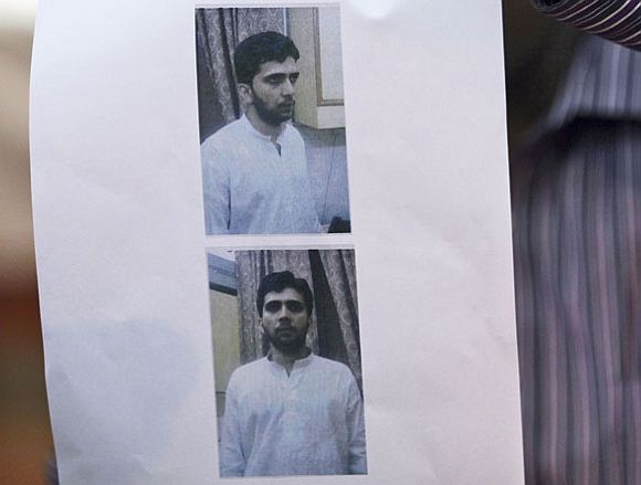 A police officer shows a recent photograph of Yasin Bhatkal
