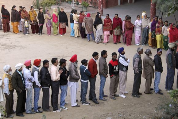 Voters line up to cast their ballots outside a polling station at Banur in Punjab, on Monday