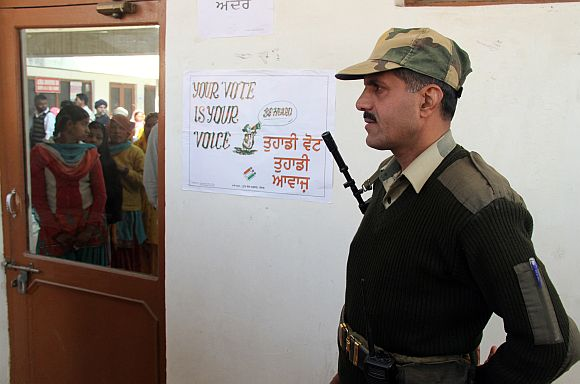 BSF trooper stands guard as voters are reflected in window as they wait to cast their ballots at polling station at Banur, Punjab, on Monday