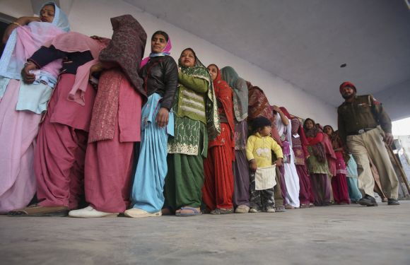 Voters wait in a queue to cast their ballots as a policeman walks past outside a polling station at Banur, on Monday