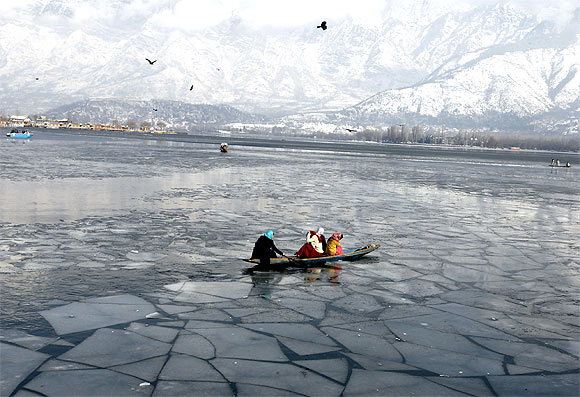 Kashmiri women row a boat at the frozen Dal Lake in Srinagar