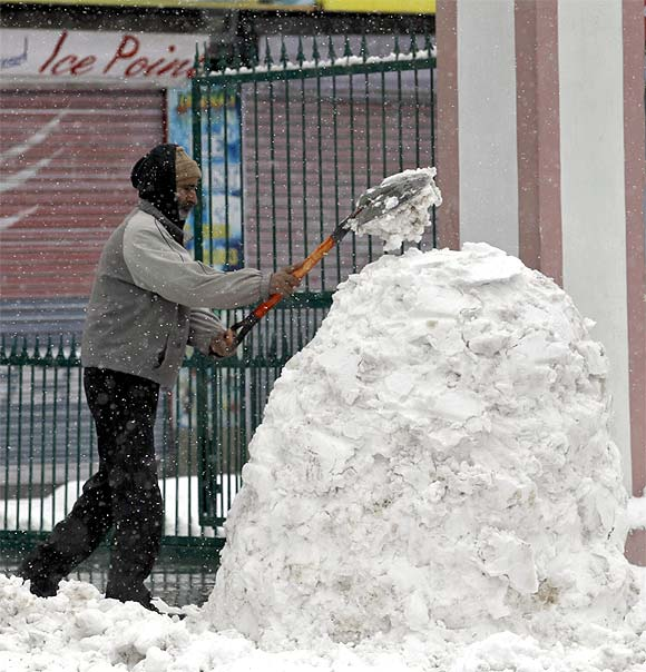 A man shovels snow into a heap outside his shop during snowfall in Srinagar
