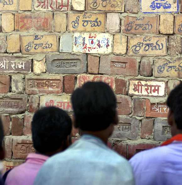 Hindu activists look at a temple wall where devotees have written the name of  Lord Ram in Ayodhya