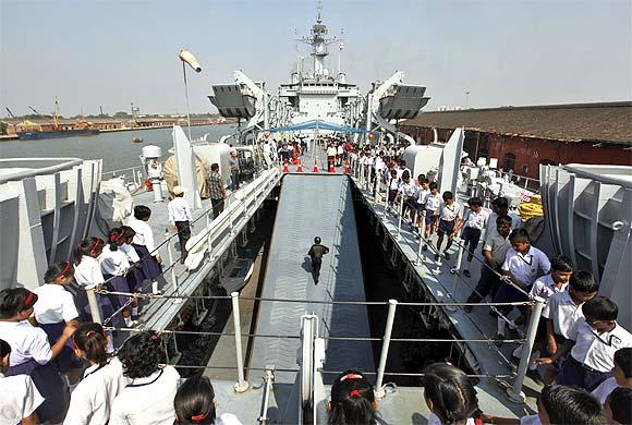 School children walk on Indian Naval Ship Airavat