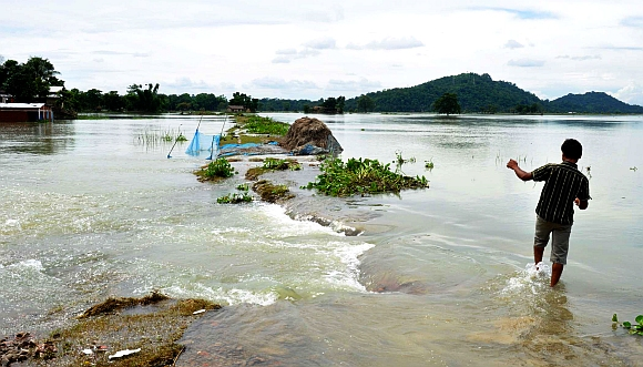 A man walks through a submerged village road at the flood affected Dupugi Jaanpump Village, about 50 km from Guwahati