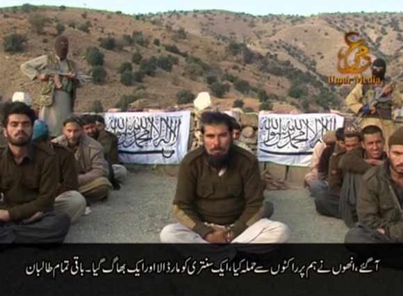 Handcuffed Pakistani soldiers with Taliban fighters in this still image taken from a video
