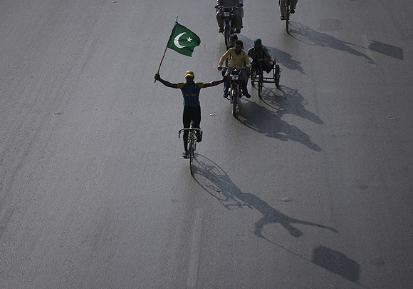 A supporter of the Pakistan People's Party holds the country's national flag while cycling during an anti-US rally