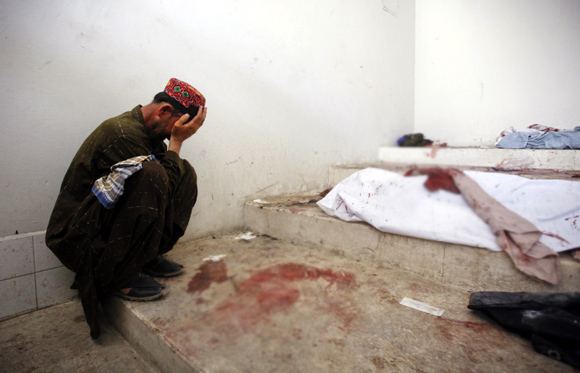 A man mourns next to his dead relative at a morgue, after his body was recovered from the site of a double suicide bombing in Quetta