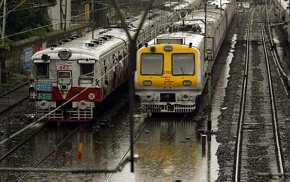 Trains move through flooded tracks after heavy rains in Mumbai