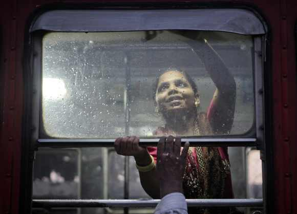 A commuter is helped by her relative while she tries to shut the window of a bus as it rains in Mumbai