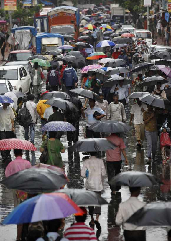 People carry umbrellas as they walk through a street during monsoon rains in Mumbai