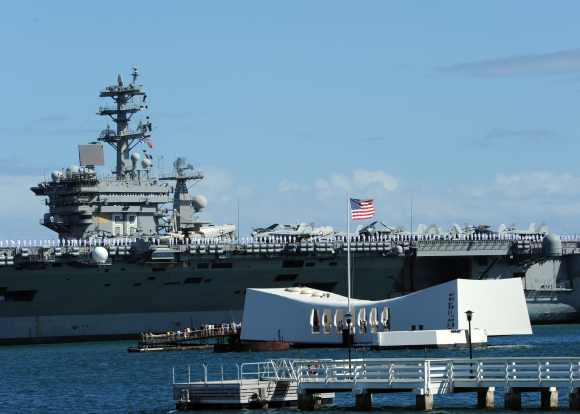The aircraft carrier USS Nimitz passes the USS Arizona Memorial in Pearl Harbor. Nimitz is participating in the biennial Rim of the Pacific exercise 2012, the world's largest international maritime exercise