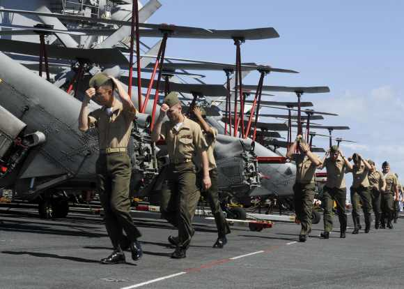 Marines from Marine Fighter Attack Squadron 323 prepare to man the rails as the aircraft carrier USS Nimitz enters Pearl Harbour