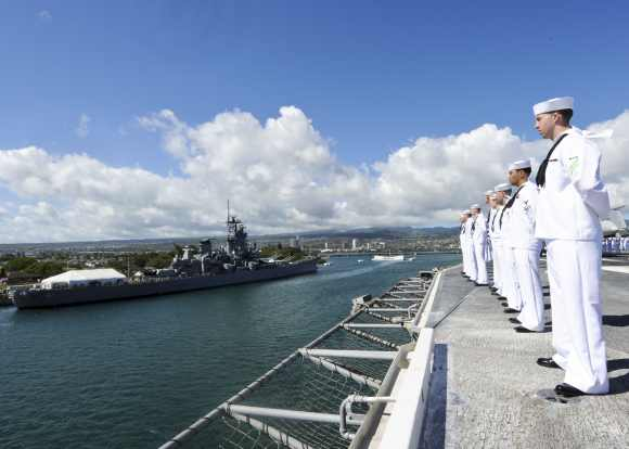 Sailors stand at parade rest as the aircraft carrier USS Nimitz passes the USS Missouri Battleship Memorial and the USS Arizona Memorial in Pearl Harbor