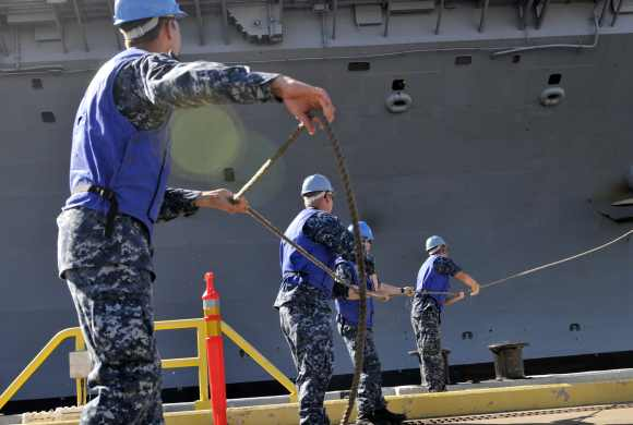 Sailors participate in mooring the aircraft carrier USS Nimitz as it pulls into Joint Base Pearl Harbor-Hickam in support of Rim of the Pacific 2012