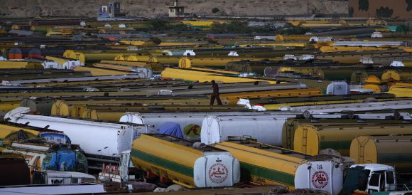 A man walks atop of fuel tankers, which were used to carry fuel for NATO forces in Afghanistan, parked at a compound in Karachi
