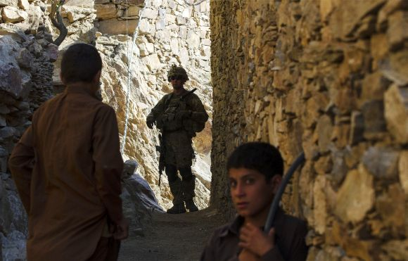 A US soldier looks back down an alleyway during patrol in Pech River Valley of Kunar Province in Afghanistan