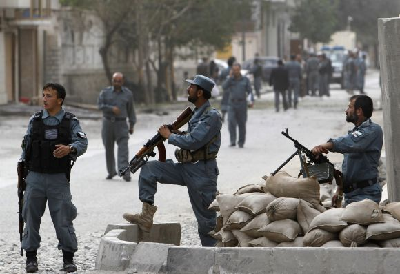 Afghan policemen take positions after a Taliban-triggered suicide blast in Kabul