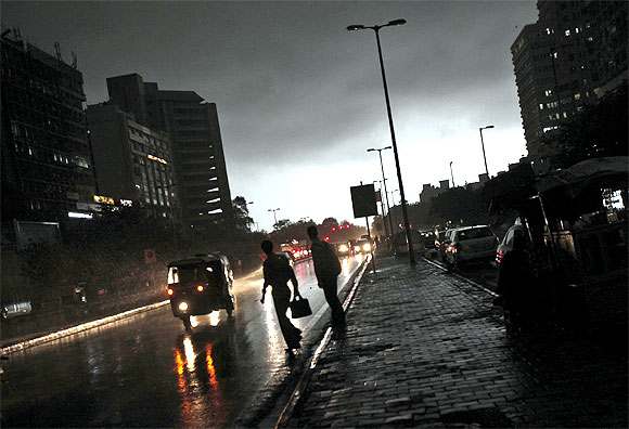 Commuters cross a street during monsoon rains in New Delhi