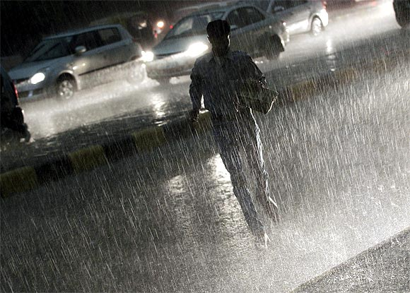 A commuter runs for cover as he crosses a road during monsoon rains in New Delhi