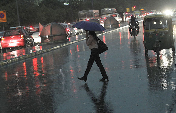 A woman holds an umbrella to shield herself from the rain as she crosses a road during a monsoon shower in New Delhi
