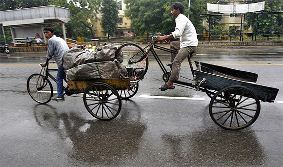 man rides a rickshaw while pulling an unused rickshaw on a road after a rain shower