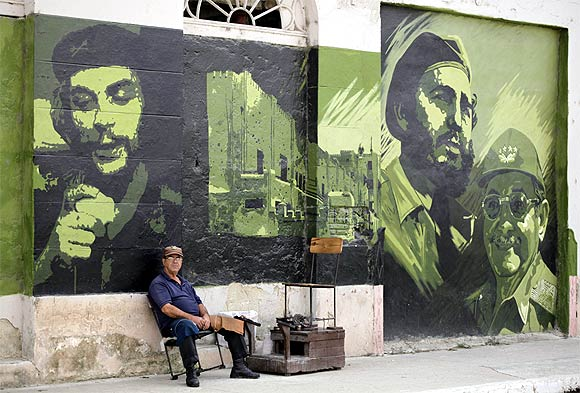 A man waits for customers at his shoe-cleaning stall beside a mural with images of revolution leader Che Guevara, former Cuban leader Fidel Castro and current President Raul Castro in Sagua La Grande, around 240 km east of Havana
