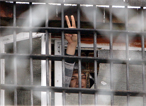 A Belarussian detainee arrested in protests gestures from a prison cell at a detention centre in Minsk