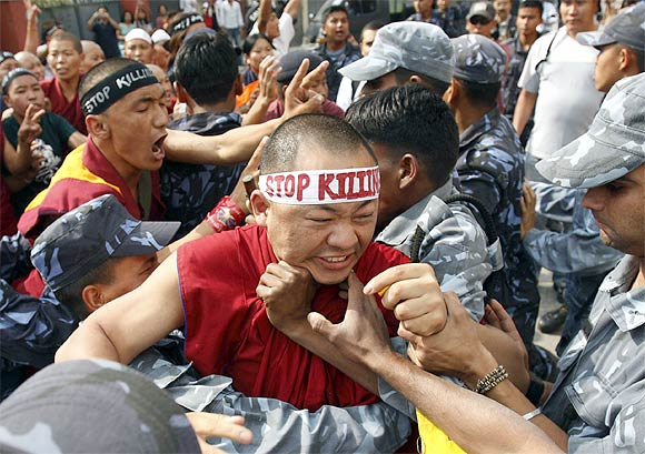 Police arrest a protesting monk outside the Chinese Embassy Visa Section in Kathmandu