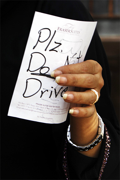 Female driver Azza Al Shmasani holds a note, which according to her, was placed on her car by an unknown person, in Saudi Arabia