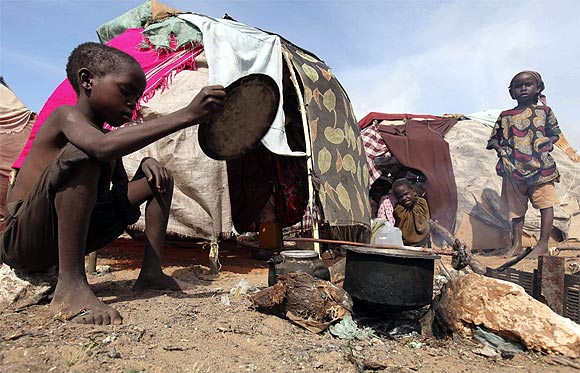 An internally displaced child prepares fire outside their makeshift shelter at a temporary camp in Hodan district of Somalia's capital Mogadishu