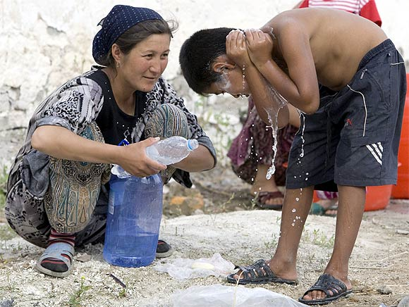 Ethnic Uzbek refugees, fled from clashes in Osh, wash themselves at a refugee camp near the Kyrgyz-Uzbek border, after escaping to Uzbekistan, in the village of Yorkishlak, some 400 km east of Tashkent
