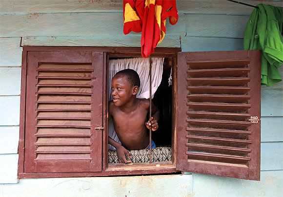 A boy looks through a window in Malabo, the capital of Equatorial Guinea