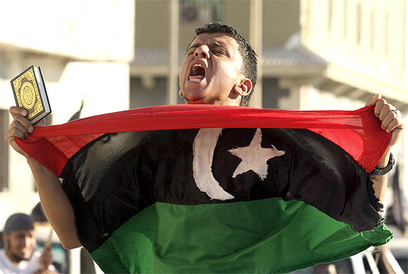 -A man carries a Koran and a Kingdom of Libya flag during a demonstration in Benghazi June 7, 2012  to demand the application of Islamic law, or Sharia law, in Libya