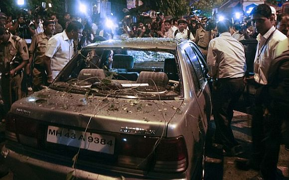 Policemen surround a vehicle which was damaged at the site of an explosion
