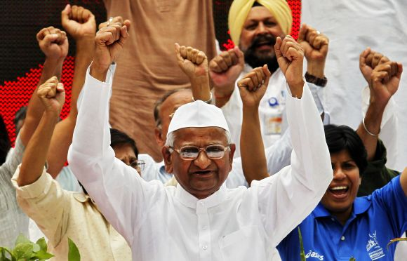 Anna Hazare raises his hands as he shouts slogans with supporters during an anti-corruption demonstration in New Delhi