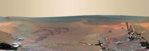 From fresh rover tracks to an impact crater blasted billions of years ago, a newly completed view from the panoramic camera on NASA's Mars Exploration Rover Opportunity shows the ruddy terrain around the outcrop where the long-lived explorer spent its most recent Martian winter