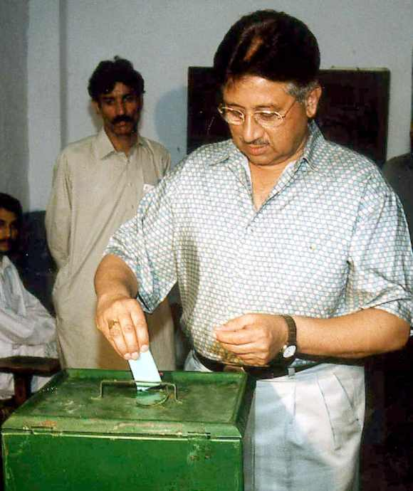 Former Pakistan President General Pervez Musharraf casts his ballot at a national park road polling station in Rawalpindi October 10, 2002
