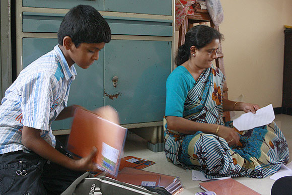 Sheela Seth helps her son Mohit as he readies to leave for his tuition classes.