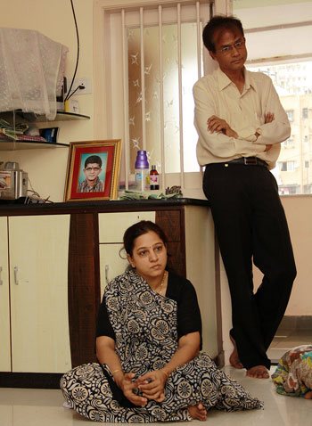 Sister-in-law Aruna and brother-in-law Shailendra. Mukeshbhai's photo is placed on the table in the room.