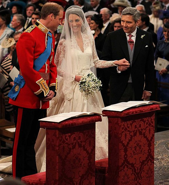 Britain's Prince William stands at the altar with his bride, Kate Middleton, and her father Michael, during their wedding ceremony at Westminster Abbey in central London April 29, 2011