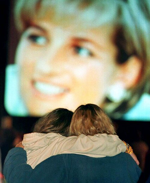 Two Atlanta women embrace September 6 as they watch the funeral coverage of Diana, Princess of Wales on a large screen television in an early morning gathering at a park in Atlanta