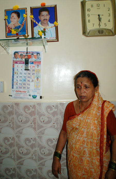 Tushar's mother standing under the portraits of her dead daughter and son Tushar