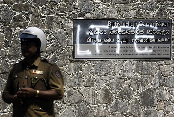 A policeman stands in front of a sign outside the British High Commission that has been spray-painted LTTE in Colombo