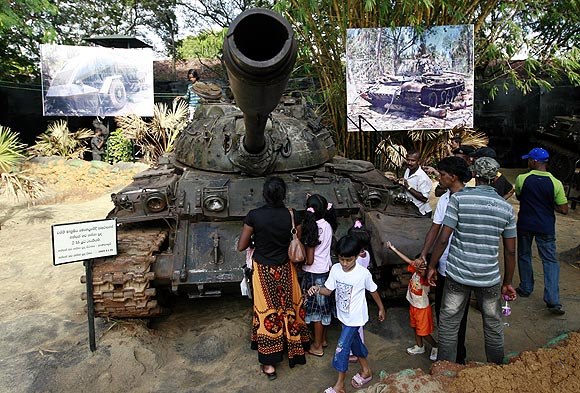 Members of the public look at a Liberation Tigers of Tamil Eelam tank captured during the war, in Colombo