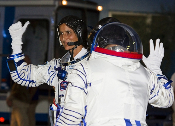 International Space Station crew member United States astronaut Sunita Williams waves after reporting to members of the State Committee before the launch of the Soyuz TMA-05M spacecraft at Baikonur cosmodrome