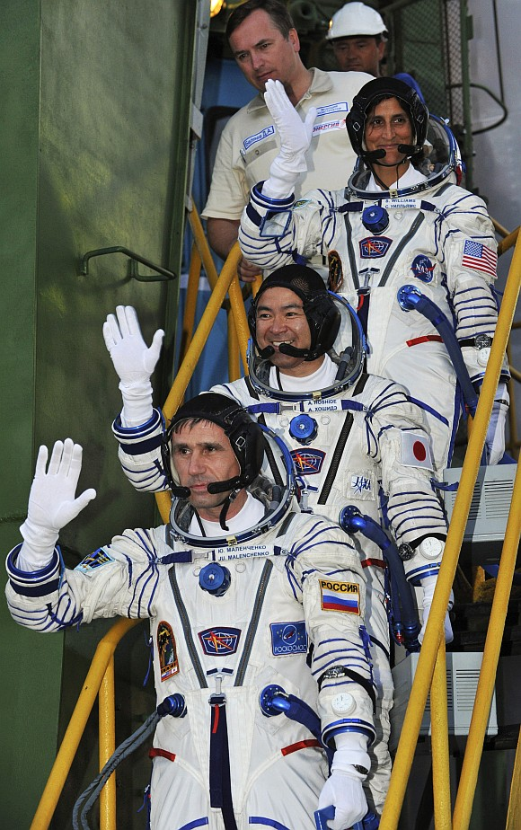 ISS crew members Russian cosmonaut Yuri Malenchenko (bottom), Japanese astronaut Akihiko Hoshide (centre) and US astronaut Sunita Williams wave as they board the Soyuz TMA-05M spacecraft at Baikonur cosmodrome