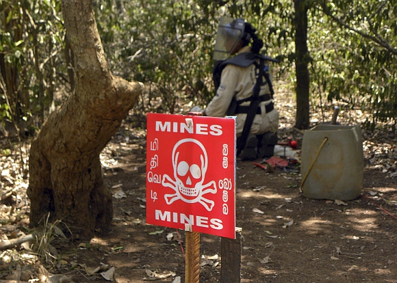 A de-miner searches for mines in a mine field in Kannaddi, located in Mannar district in Sri Lanka