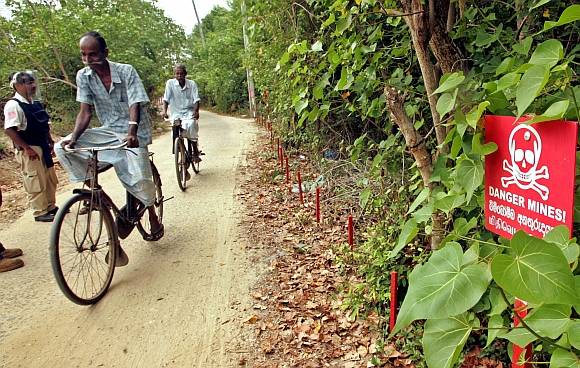 Sri Lankans cycle near a minefield in Irupalai, on the outskirts of Jaffna