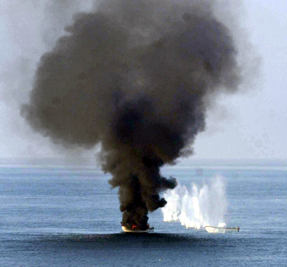 Small boats being towed by a suspected pirate mothership are destroyed February 2, 2011 by weapons fire from the guided-missile destroyer USS Momsen